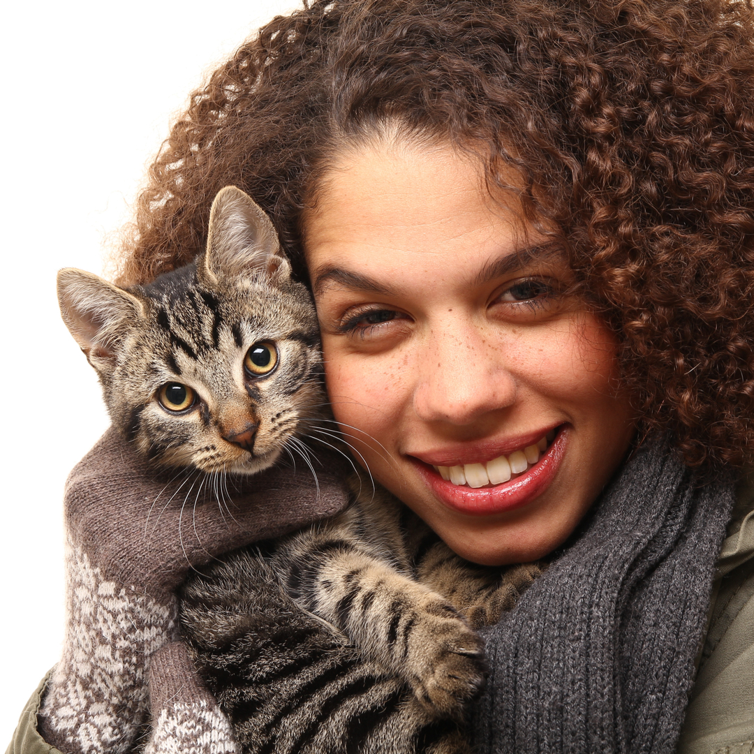 African-American woman holding young tabby cat on her shoulder